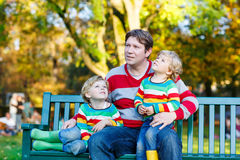 Two little kid boys and young father sitting together Stock Photos
