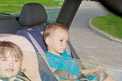 Two little kids on back seat in child safety seat Stock Photo