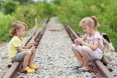 Two little kids with backpack sitting on the railway Royalty Free Stock Photography