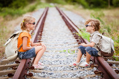 Two little kids with backpack sitting on the railway Royalty Free Stock Image