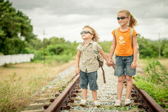 Two little kids with backpack standing on the railway Stock Photo