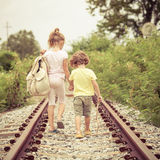 Two little kids with backpack standing on the railway Royalty Free Stock Image
