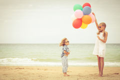 Two little kids with balloons standing on the beach Royalty Free Stock Photography