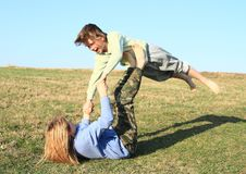 Two kids playing and exercising yoga on meadow royalty free stock image