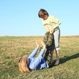 Two kids playing and exercising yoga on meadow stock image