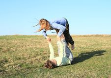 Two kids playing and exercising yoga on meadow royalty free stock photo