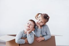 Two a little kids boy and girl playing in cardboard boxes. Concept photo. Children have fun.  Stock Photography