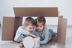 Two a little kids boy and girl playing in cardboard boxes. Concept photo. Children have fun.  Stock Photos