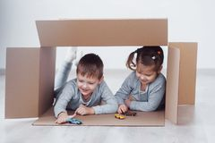Two a little kids boy and girl playing small cars in cardboard boxes. Concept photo. Children have fun. Concept photo. Two a little kids boy and girl playing Stock Photo