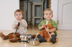 Two little kids boy and girl sitting on the kitchen floor playin. G with pots and pans, kids have fun, happy kids concept Royalty Free Stock Photography