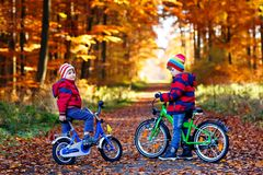Two little kids boys, best friends having fun in autumn park with bicycles Stock Photo