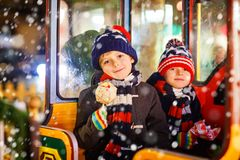 Two little kids boys on carousel at Christmas market Royalty Free Stock Photography