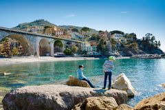 Two little kids boys climbing on stones on beach of Mediterranean sea in Liguria region, Italy. Siblings brothers in royalty free stock photography