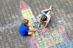 Two little kids boys drawing knight castle with colorful chalks on asphalt. Happy siblings and friends having fun with. Creating chalk picture and painting stock images