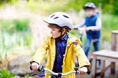 Two little kids boys driving and running on bicycles in park stock images