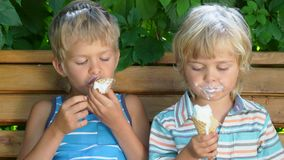 Two little kids boys eating ice cream. In summer day stock video