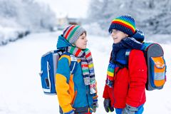 Two little kids boys of elementary class walking to school during snowfall. Happy children having fun and playing with royalty free stock photos