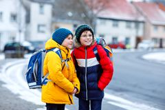 Two little kids boys of elementary class walking to school during snowfall. Happy children having fun and playing with stock images
