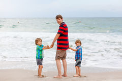 Two little kids boys and father on the beach of ocean Stock Photo
