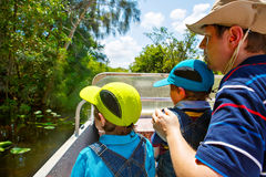 Two little kids boys and father making air boat tour in Everglades Park. Two little kids boys and father making air boat tour in Florida wetland swamp at Royalty Free Stock Photography