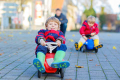 Two little kids boys and father playing with cars, outdoors Stock Photos