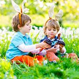 Two little kids boys and friends in Easter bunny ears during traditional egg hunt in spring garden, outdoors. Siblings. Eating chocolate cake, muffin and stock photos