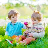 Two little kids boys and friends in Easter bunny ears during traditional egg hunt in spring garden, outdoors. Siblings. Having fun with finding colorful eggs stock photos