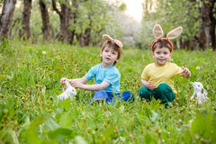 Two little kids boys and friends in Easter bunny ears during traditional egg hunt in spring garden, outdoors. Siblings having fun Royalty Free Stock Photography