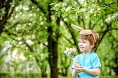 Two little kids boys and friends in Easter bunny ears during traditional egg hunt in spring garden, outdoors. Siblings having fun Stock Photography