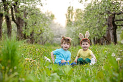 Two little kids boys and friends in Easter bunny ears during traditional egg hunt in spring garden, outdoors. Siblings having fun Royalty Free Stock Image