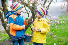 Two little kids boys and friends making traditional Easter egg hunt royalty free stock photography
