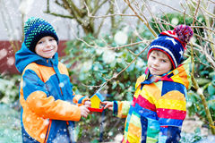 Two Little Kids Boys Hanging Bird House On Tree For Feeding In Winter Royalty Free Stock Image