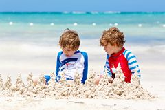 Two little kids boys having fun with building a sand castle on tropical beach of carribean island. royalty free stock photos