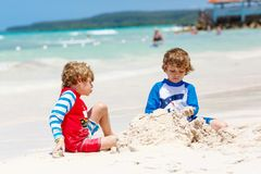 Two little kids boys having fun with building a sand castle on tropical beach of carribean island. stock image