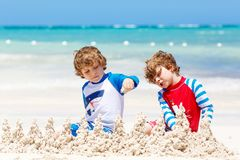 Two little kids boys having fun with building a sand castle on tropical beach of carribean island. children playing. Together on their vacations Twins, Happy royalty free stock photo