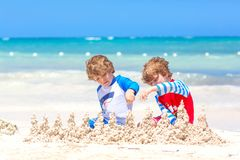 Two little kids boys having fun with building a sand castle on tropical beach on island. Healthy children playing royalty free stock image