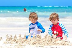 Two little kids boys having fun with building a sand castle on tropical beach on island. Healthy children playing. Together on their vacations. Twins, Happy stock image