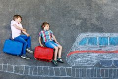 Two little kids boys having fun with train picture drawing with colorful chalks on asphalt. Children having fun with royalty free stock images