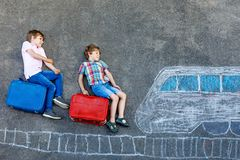 Two little kids boys having fun with train picture drawing with colorful chalks on asphalt. Children having fun with royalty free stock photography