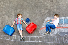 Two little kids boys having fun with train picture drawing with colorful chalks on ground Stock Photos