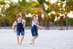 Two little kids boys having fun on tropical beach, happy best friends playing, friendship concept. Siblings brothers stock photo