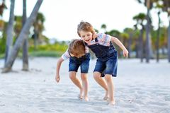 Two little kids boys having fun on tropical beach, happy best friends playing, friendship concept. Siblings brothers royalty free stock photography