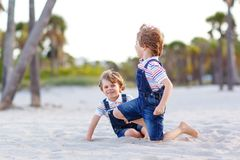 Two little kids boys having fun on tropical beach, happy best friends playing, friendship concept. Siblings brothers stock image
