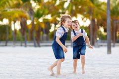 Two little kids boys having fun on tropical beach, happy best friends playing, friendship concept. Siblings brothers royalty free stock images