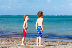 Two little kids boys having fun on tropical beach Stock Photos