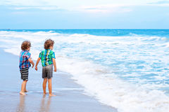 Two little kids boys looking on sunset on the beach of ocean Royalty Free Stock Photos