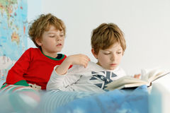 Two little kids boys in pajamas reading a book in bed. Excited siblings in nightwear. One brother boy reading loud and another child hearing. Family Stock Images
