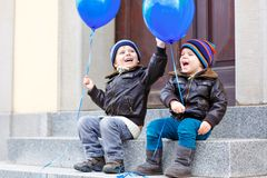 Two little kids boys playing with blue air balloons outdoors. Happy twins and toddler brothers smiling and laughing stock image