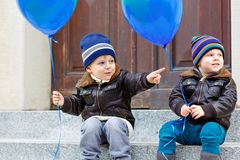 Two little kids boys playing with blue air balloons outdoors. Happy twins and toddler brothers smiling and laughing royalty free stock image