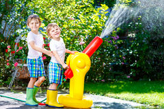 Two little kids boys playing with a garden hose water sprinkler. Two little kids boys playing with a garden hose sprinkler on hot and sunny summer day. Children royalty free stock photo